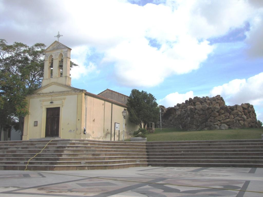 Vlevo křesťanský kostel, vpravo megalitický nuragh.