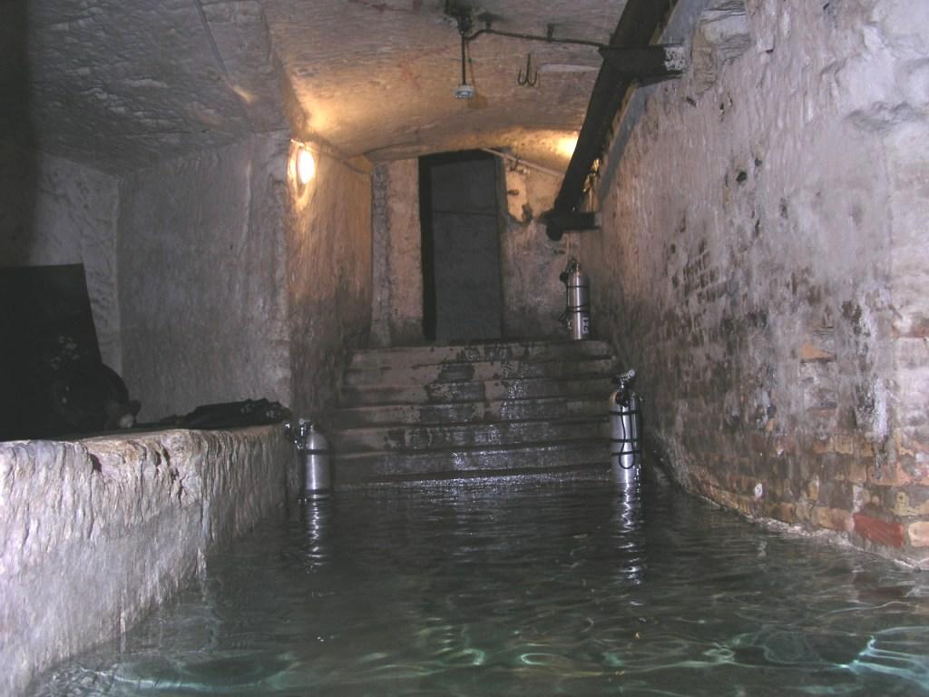 Vstup do zatopené chodby. Na schodech jsou připraveny potápěčské tlakové lahve.